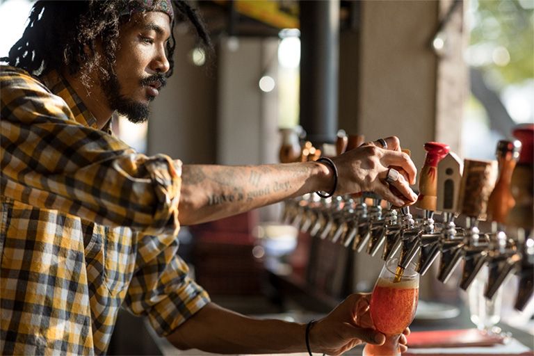 server pouring a drink from tap